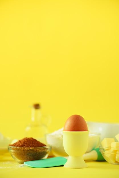 Ingrédients de cuisson sains - beurre, sucre, farine, œufs, huile, cuillère, rouleau à pâtisserie, pinceau, fouet, lait sur fond jaune. Photo Premium