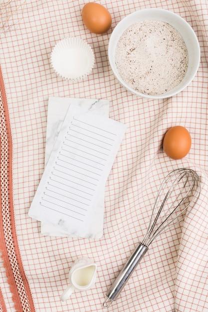Ingrédients de cuisson sains avec une liste de contrôle vide sur une serviette de cuisine Photo gratuit