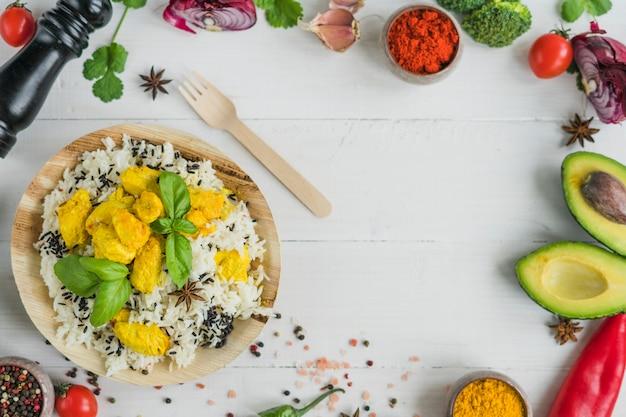 Ingrédients frais et riz frit dans une assiette en bois avec une fourchette sur la table Photo gratuit