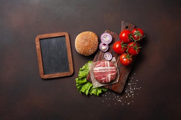 Ingrédients hamburger crue côtelette, tomates, laitue, pain, fromage, concombres et oignons sur fond rouillé Photo Premium