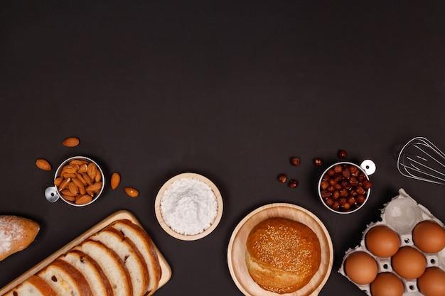 Ingrédients de pains faits maison, farine, noix d'amande, noisettes, oeufs sur fond sombre. Photo Premium