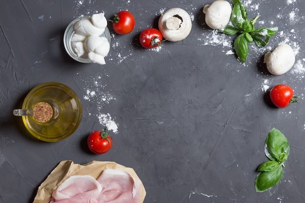 Ingrédients de la pizza sur le fond gris avec espace de copie au centre, pâte, tomates, champignons, basilic, jambon Photo Premium