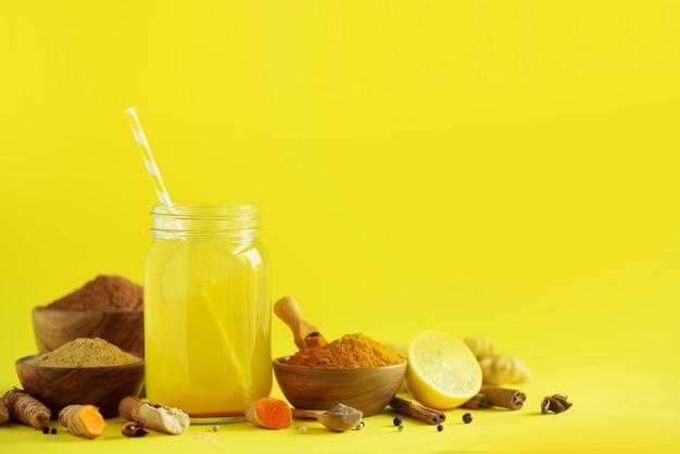 Ingrédients pour boisson au curcuma orange sur fond jaune. eau citronnée au gingembre, curcuma, poivre noir. concept de boisson chaude végétalienne Photo Premium