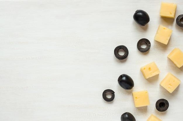 Ingrédients pour les collations, fromage aux olives sur une table blanche Photo Premium