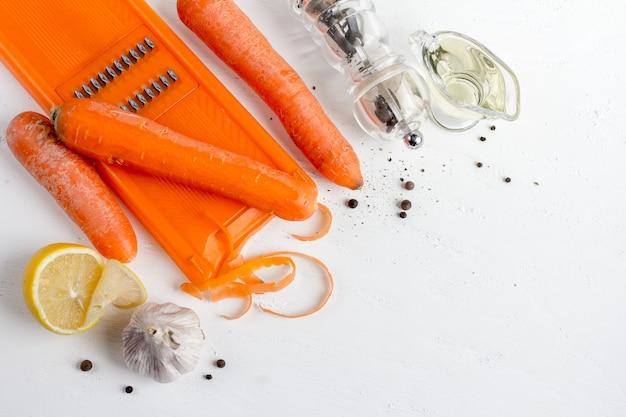 Les ingrédients pour cuisiner des carottes coréennes: carottes, beurre, piment, coriandre, citron sur une table blanche. Photo Premium