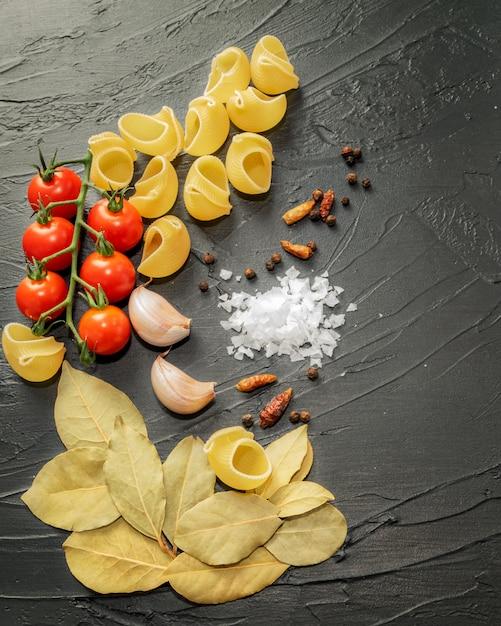Ingrédients Pour La Cuisson De Coquilles De Pâtes Aux épices Et Tomates Cerises Sur Fond Noir. Photo Premium