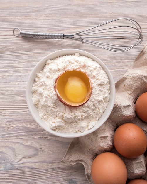 Ingrédients Pour La Cuisson: Farine, œufs Et Jaune Sur Une Table. Photo Premium