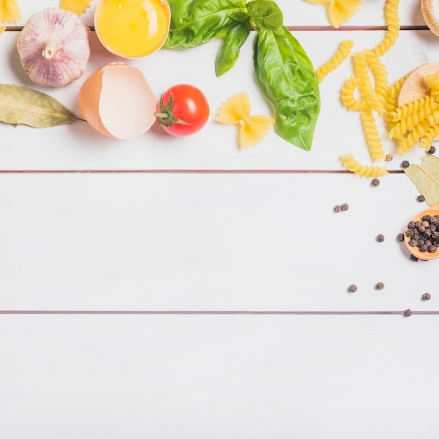 Ingrédients pour faire des pâtes faites maison crues sur une planche en bois Photo gratuit