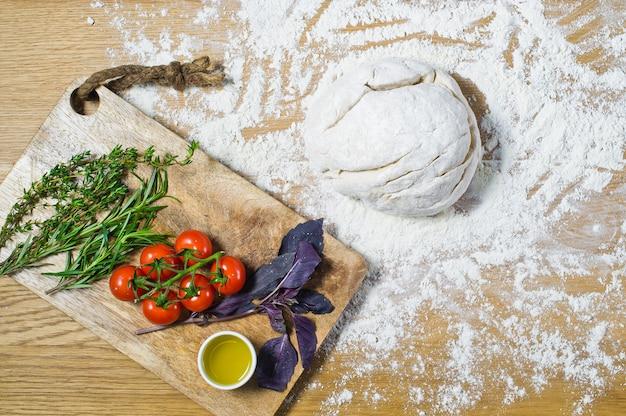 Ingrédients pour focaccia: pâte, tomates, romarin, thym, basilic, huile d'olive sur une table en bois. Photo Premium
