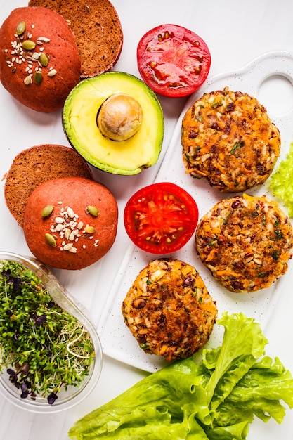 Ingrédients pour hamburgers végétaliens sur hamburgers aux haricots blancs, pains à la betterave rose, choux, avocats et légumes, Photo Premium