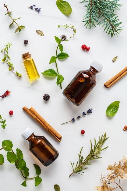 Ingrédients pour l'huile essentielle. différentes herbes et bouteilles d'huile essentielle, fond blanc, flatlay. Photo Premium