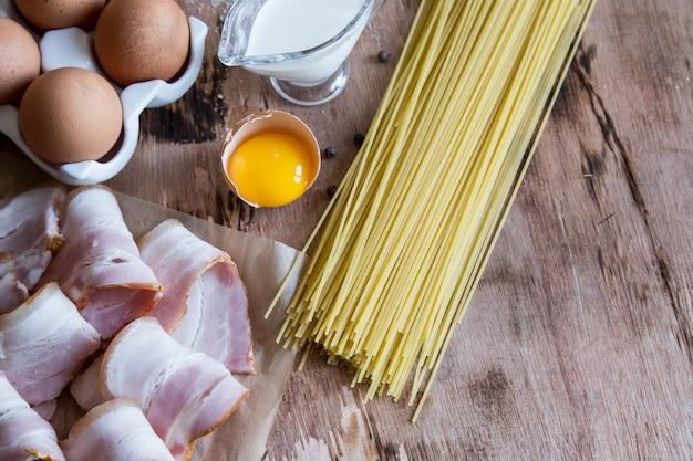Ingrédients pour pâtes carbonara avec bacon, fromage, crème et jaune sur table en bois Photo Premium