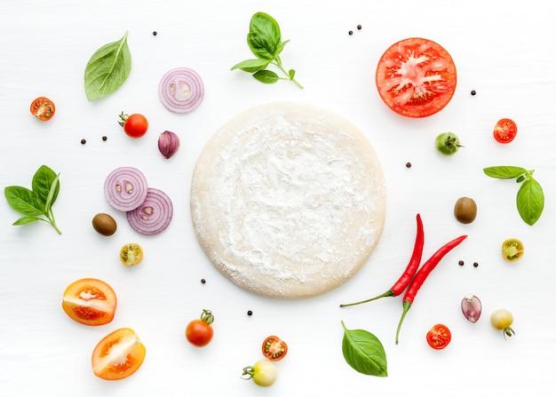Les ingrédients pour une pizza maison sur un fond en bois blanc. Photo Premium