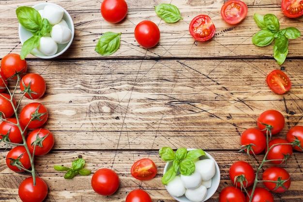 Les ingrédients pour une salade caprese. basilic, boules de mozzarella et tomates avec espace de copie. Photo Premium
