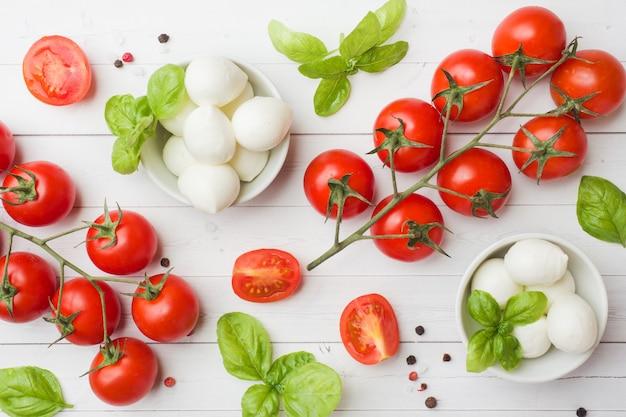 Les ingrédients pour une salade caprese. basilic, boulettes de mozzarella et tomates Photo Premium