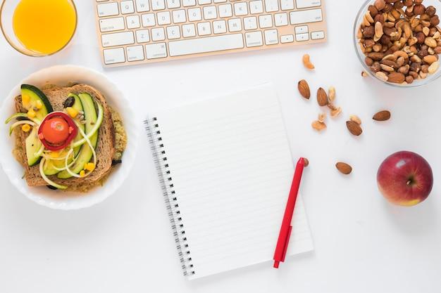Ingrédients pour sandwich; jus; fruits secs; pomme et bloc-notes vide avec un stylo sur fond blanc Photo gratuit