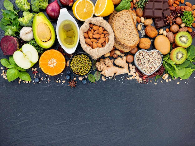 Ingrédients Pour La Sélection D'aliments Sains Mis En Place Sur Fond De Pierre Sombre. Photo Premium