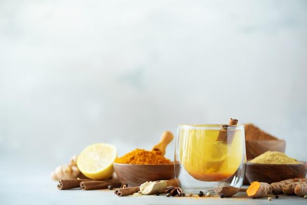 Ingrédients pour thé chaud au curcuma sur fond gris. boisson ayurvédique saine au citron, gingembre, cannelle, curcuma. Photo Premium