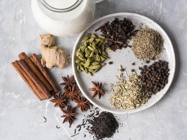 Ingrédients pour le thé masala sur fond gris. vue de dessus Photo Premium