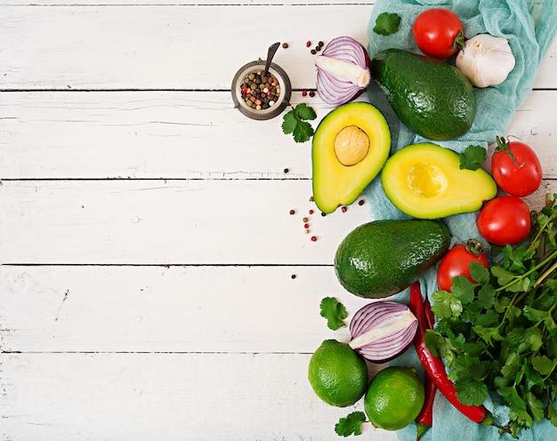 Ingrédients De La Sauce Guacamole - Avocat, Tomate, Oignon, Piment, Ail, Coriandre, Citron Vert Sur Fond Blanc. Vue De Dessus Photo Premium