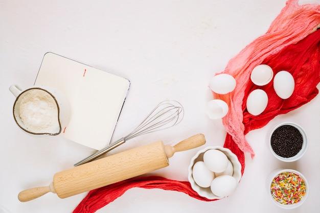 Ingrédients et ustensiles de cuisine près du cahier Photo gratuit