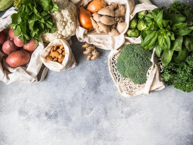 Ingrédients végétaliens sains pour la cuisine. divers légumes et herbes sains et propres dans des sacs tissés. produits du marché sans plastique. concept zéro déchet à plat. espace de copie Photo Premium