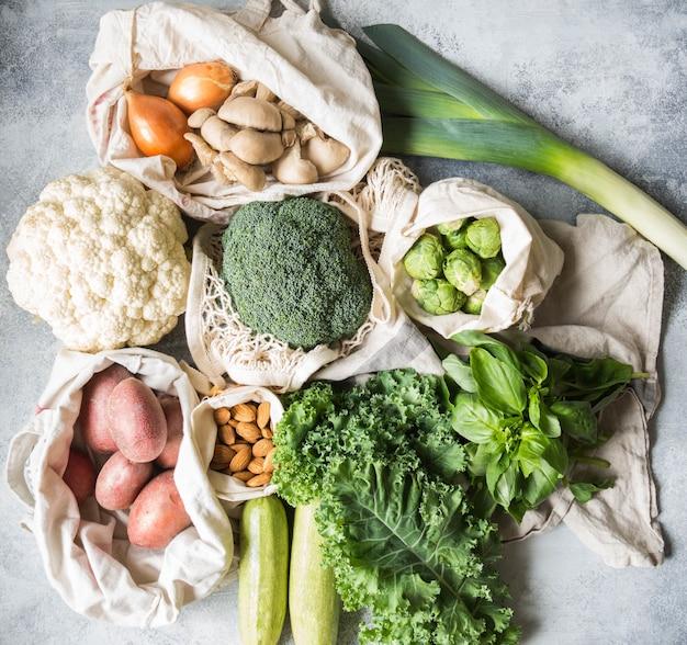 Ingrédients végétaliens sains pour la cuisine. divers légumes et herbes sains et propres dans des sacs tissés. produits du marché sans plastique. concept zéro déchet Photo Premium