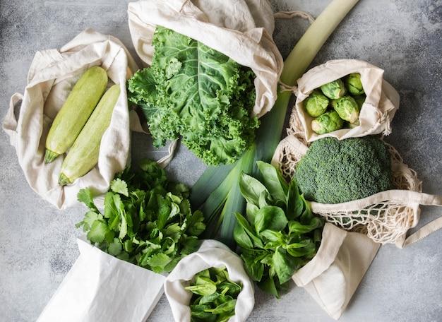 Ingrédients végétaliens sains et verts pour la cuisine. divers légumes verts et herbes propres dans des sacs en textile. produits du marché sans plastique. concept zéro déchet à plat. Photo Premium