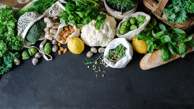 Ingrédients végétariens sains pour la cuisine. divers légumes propres, herbes, noix et pain sur fond de marbre. produits du marché sans plastique. lay plat. espace de copie Photo Premium