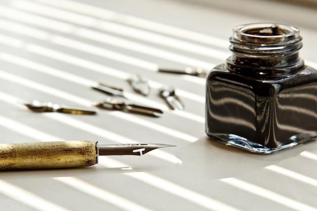 Inkpot avec embouts métalliques pour le stylo à encre sur fond blanc à rayons solaires. Photo Premium