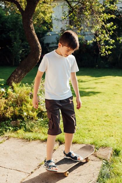 Innocent garçon jouant à la planche à roulettes dans le parc Photo gratuit