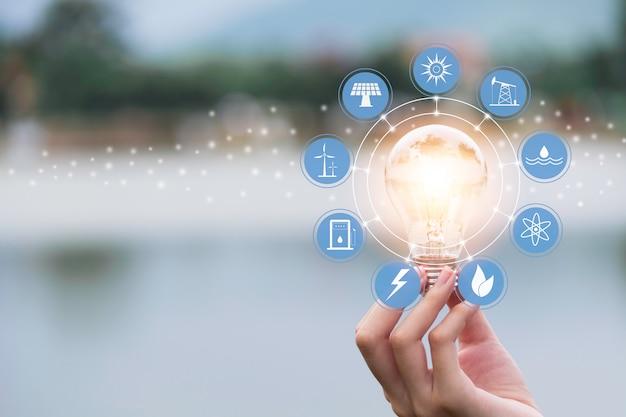 Innovation et concept énergétique de la main tenir une ampoule Photo Premium