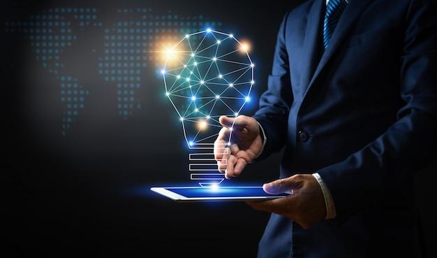 Innovation et technologie, homme d'affaires tenant une tablette avec ligne de connexion créative et ampoule d'éclairage Photo Premium