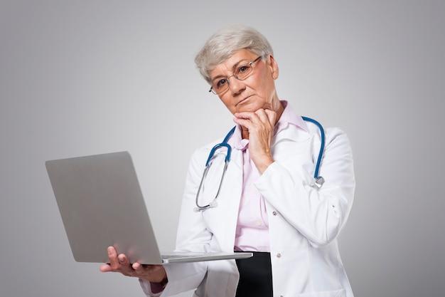 Inquiet Femme Médecin Senior Avec Ordinateur Portable Photo gratuit