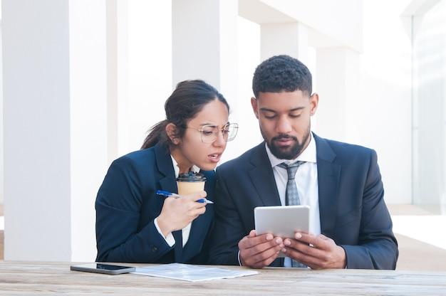 Inquiet des gens d'affaires à l'aide de la tablette et travaillant au bureau Photo gratuit