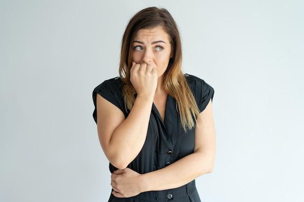 Inquiet jeune femme se ronger les ongles tout en ayant de l'anxiété. Photo gratuit