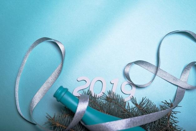 Inscription 2019 avec une bouteille bleue et un ruban sur la table Photo gratuit