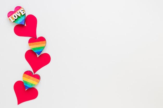 Inscription D'amour Avec Petits Coeurs De Papier Et Arc-en-rouge Photo gratuit
