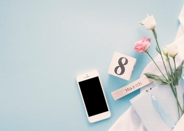 Inscription du 8 mars avec des fleurs et smartphone sur table Photo gratuit