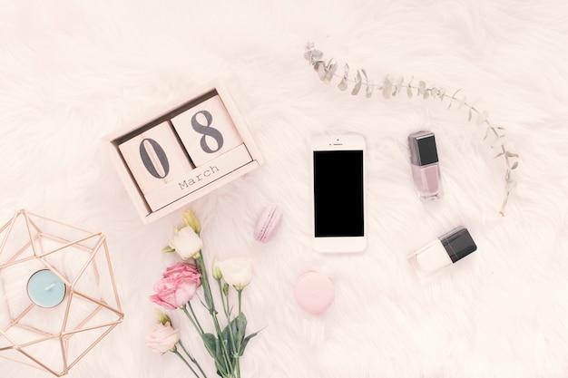 Inscription du 8 mars avec smartphone, fleurs et bonbons sur une couverture Photo gratuit