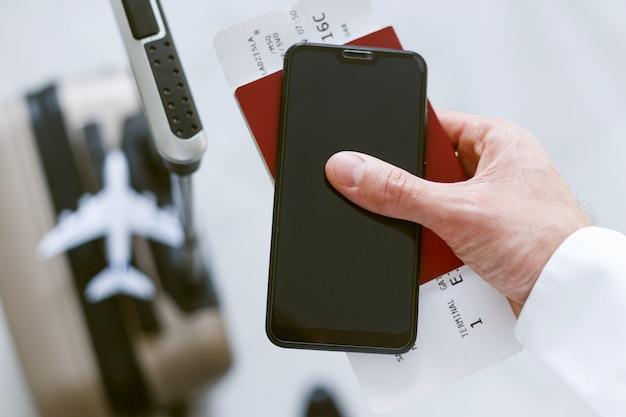 Inscription électronique Via Smartphone Pour Embarquer Dans L'avion. Homme Avec Une Valise Détient Un Billet De Téléphone Et Un Passeport. Photo Premium