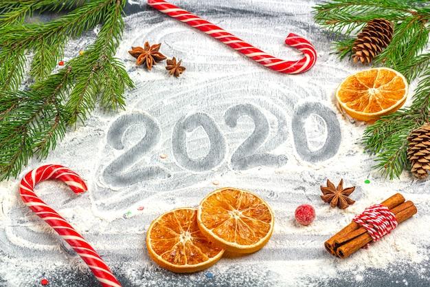 Inscription Happy New Year 2020 Et Cadre De Branches De Sapin, Cônes, Anis étoilé, Cannelle Et Oranges Séchées Photo Premium