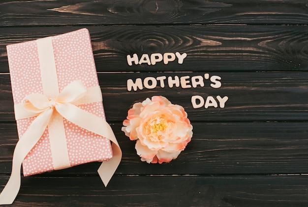 Inscription heureuse fête des mères avec boîte-cadeau et fleur Photo gratuit