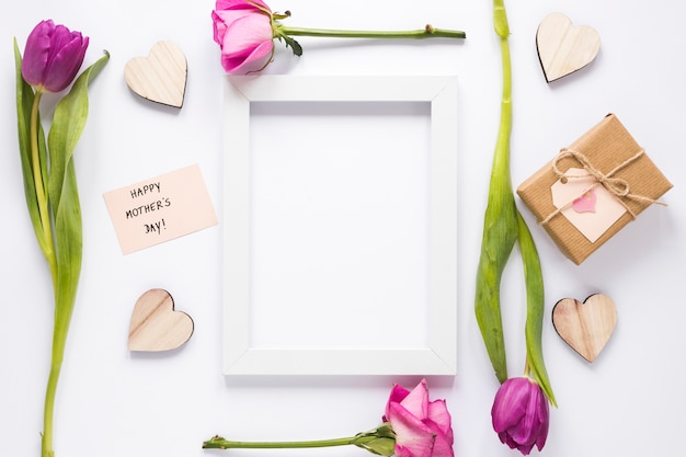 Inscription heureuse fête des mères avec des fleurs et un cadre Photo gratuit