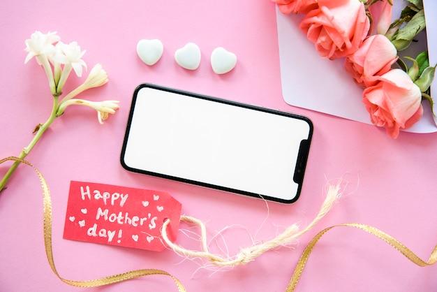 Inscription heureuse fête des mères avec smartphone et fleurs Photo gratuit