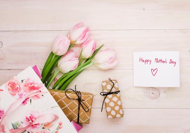 Inscription heureuse fête des mères avec des tulipes et des cadeaux Photo gratuit