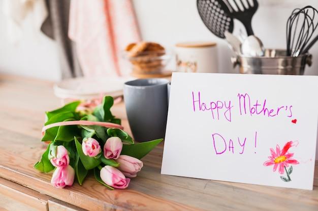 Inscription heureuse fête des mères avec des tulipes sur table Photo gratuit