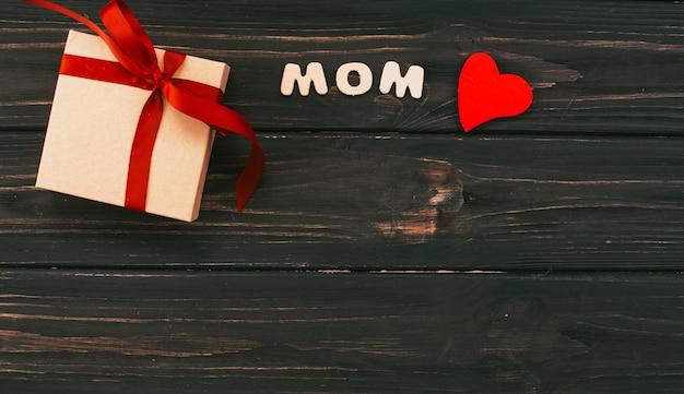 Inscription de maman avec une boîte cadeau sur une table en bois Photo gratuit