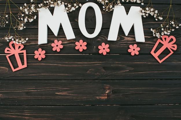 Inscription de maman avec des branches de fleurs et des cadeaux sur la table Photo gratuit