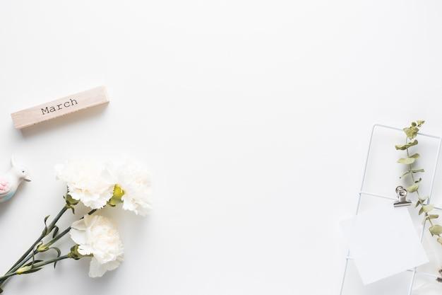 Inscription de mars avec des fleurs d'oeillets et du papier Photo gratuit